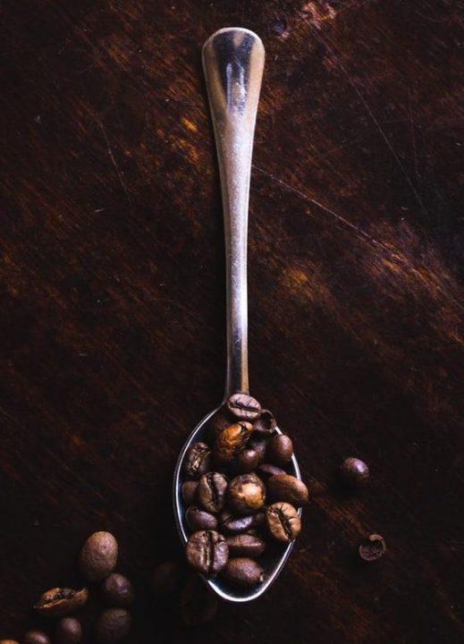 łyżeczka z ziarnami kawy na drewnianym ciemnym stole